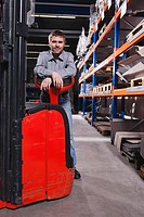 Germany, Neukirch, Foreman leaning on forklift truck, portrait