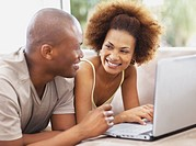 Couple smiling on couch with a laptop