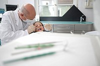Germany, Bavaria, Landsberg, Dentist and girl 8_9 in dental surgery