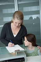 Germany, Bavaria, Landsberg, Mother and daughter 8_9, Mother filling out form at clinic reception