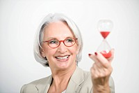 Senior Businesswoman holding sandglass, portrait