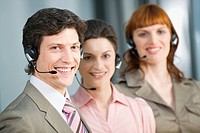 Germany, Munich, Co_workers wearing headsets, smiling, portrait