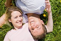 Germany, Bavaria, Munich, Young couple lying in meadow, smiling, elevated view, portrait (thumbnail)