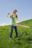 Germany, Bavaria, Munich, Girl 6_7 playing with hula_hoop