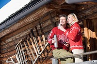 Italy, South Tyrol, Seiseralm, Couple standing on deck of log cabin, holding thermos flask