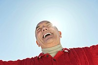 Italy, South Tyrol, Seiseralm, Senior man laughing, low angle view, portrait