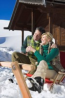 Italy, South Tyrol, Seiseralm, Couple sitting in front of log cabin, holding champagne glasses, smiling, portrait