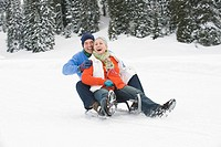 Italy, South Tyrol, Seiseralm, Senior couple sledding down hill, laughing, portrait