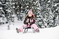 Italy, South Tyrol, Seiseralm, Girl 8_9 sitting on sledge, portrait