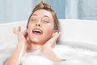 Young woman in bathtub listening to music