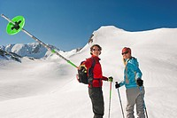 Austria, Salzburger Land, Altenmarkt, Zauchensee, Young Couple cross country skiing in mountains, man pointing with ski pole, portrait
