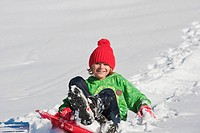 Austria, Salzburger Land, Altenmarkt, Boy 6_7 on sled, smiling, portrait