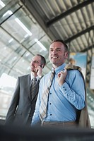 Germany, Leipzig_Halle, Airport, Two businessmen on travelator, one using mobile phone