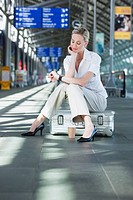 Germany, Leipzig_Halle, Young woman in Airport departure lounge, sitting on suitcase