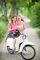 Germany, Bavaria, Young couple with map on motor scooter