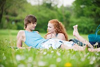 Germany, Bavaria, Young couple lying in meadow, smiling, portrait