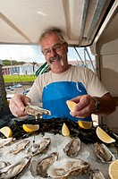 A fishmonger selling fresh oysters at The 2009 Cardigan Bay Seafood festival, Aberaeron, Ceredigion Wales UK