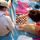 Couple playing chess on the beach at Aberystwyth on a summer evening, Wales UK