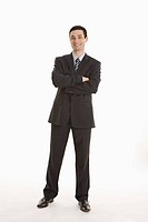 Businessman standing with arms crossed, smiling, portrait