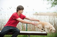 Germany, Bavaria, Ammersee, Young man and dog on bench, portrait (thumbnail)