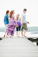 Germany, Bavaria, Ammersee, Four friends walking on jetty