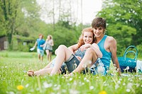 Germany, Bavaria, Young couple sitting in meadow, persons in background
