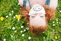 Germany, Bavaria, Young woman lying in meadow, elevated view