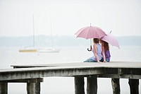 Germany, Bavaria, Ammersee, Two Women sitting on jetty, holding umbrella, rear view