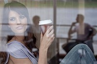 Germany, Cologne, Young woman in window of cafe