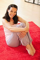 Woman sitting on floor, smiling, portrait