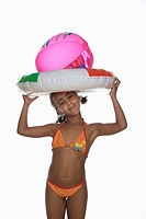 African girl 6_7 holding floating tire and beach ball, smiling, portrait