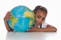 African girl 6-7 holding globe, smiling, portrait (thumbnail)