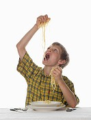 Boy 8_9 eating spaghetti