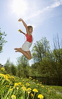 Austria, Salzkammergut, girl 10_11 jumping in garden, side view