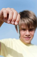 Boy 8_9 holding small fish, close_up