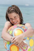 Spain, Mallorca, Girl 10_11 holding beachball, smiling, portrait