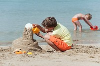 Spain, Mallorca, Boy 8_9 building sandcastle on beach, girl 4_5 in background