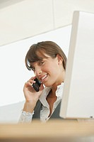 Young woman in office using telephone