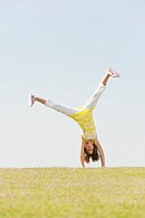 Spain, Mallorca, Girl 10_11 doing cartwheel in meadow
