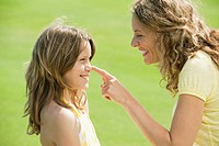 Spain, Mallorca, Mother touching daughter's 10-11 nose, smiling, side view, portrait (thumbnail)