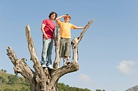 Spain, Mallorca, Father and son 8_9 standing on tree