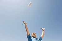Senior man throwing shoe in the air, cheering, portrait