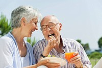 Spain, Mallorca, Senior woman feeding grapes to senior man, laughing, portrait