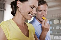 Germany, Hamburg, Couple in kitchen, man eating a piece of bell pepper, portrait, close_up