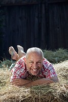 Germany, Bavaria, Senior man lying on haystack, smiling, portrait
