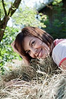 Germany, Bavaria, Woman lying in hay, smiling, portrait