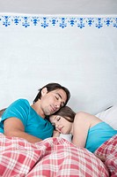 Germany, Bavaria, Young couple lying in bed
