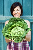 Germany, Bavaria, Woman holding savoy cabbage, smiling, portrait
