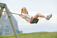 Italy, Seiseralm, Girl 6_7 sitting on swing, portrait