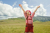 Italy, Seiseralm, Girl 8-9 in meadow cheering, arms up, portrait (thumbnail)